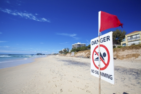 no swimming: Danger no swimming sign on eroded Australian beach
