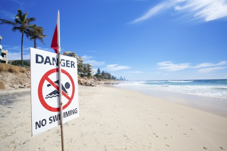 Danger no swimming sign on eroded Australian beach photo