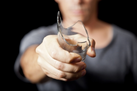 shattered glass: Man threatening with broken drink glass as weapon Stock Photo