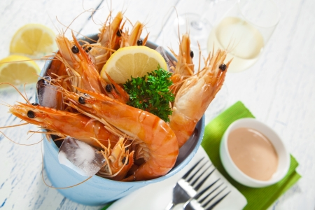 shrimp: Bucket of king prawns on ice with lemon, sauce and two glasses of wine