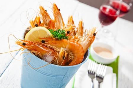 Bucket of king prawns on ice with lemon, sauce and two glasses of wine photo