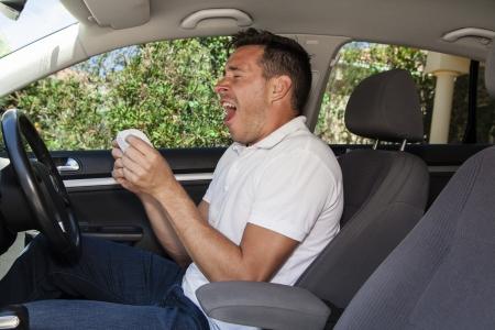 allergic reaction: Man allergic to pollen sneezing into hankie inside a car Stock Photo