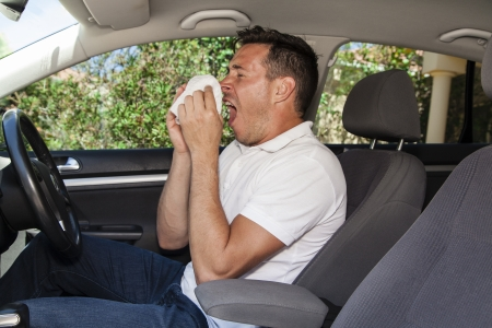 hayfever: Man allergic to pollen sneezing into hankie inside a car Stock Photo