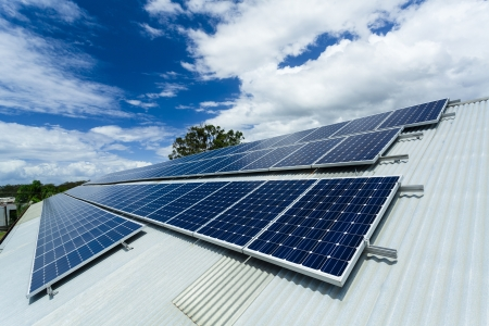 factory power generation: Solar panels on factory roof. Stock Photo