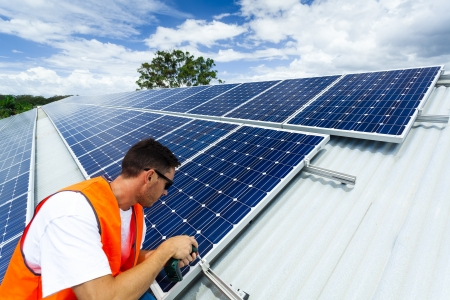 Young technician installing solar panels on factory roof Stock Photo - 18445797