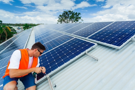 energy work: Young technician installing solar panels on factory roof