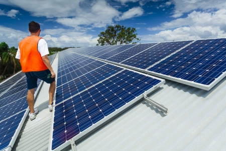carbon neutral: Young technician inspecting solar panels on factory roof