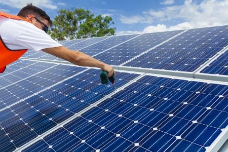 Junge Techniker Installation von Sonnenkollektoren auf Hallendach