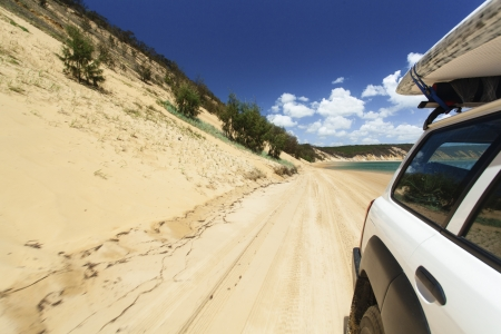 4wd: Off road vehicle with surfboard on roof driving on tropical beach Stock Photo