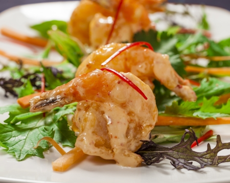 starter: Chilli tempura prawns butterflied with chilli mayo and cilantro salad Stock Photo