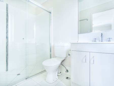 Einfaches Badezimmer mit Waschbecken, Spiegel, WC und Dusche