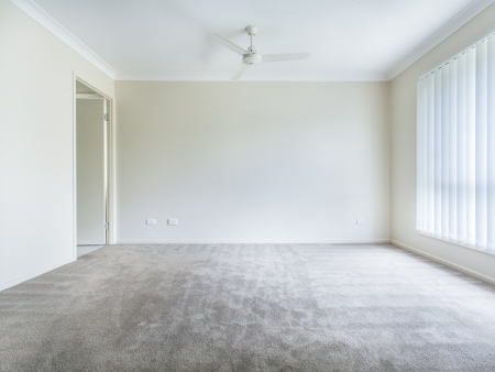 ensuite: Large empty bedroom with ceiling fan and curtains