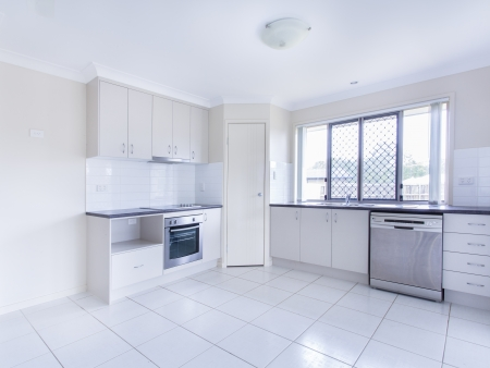 appliance: Empty tiled kitchen with dish stainless steel appliances