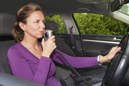 sobriety: Woman in car blowing into breathalyzer