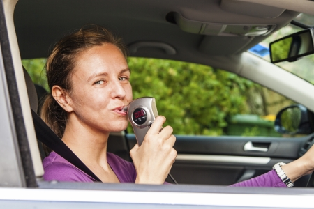 Woman in car blowing into breathalyzer photo