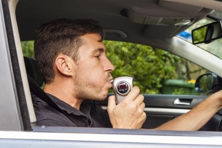 sobriety test: Man in car blowing into breathalyzer