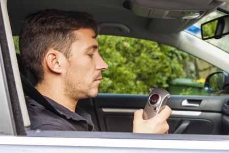 sobriety test: Man in car looking at breathalyzer