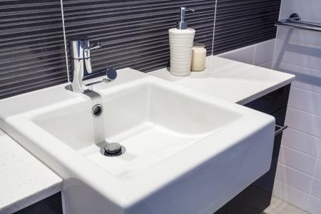 llave de agua: Primer plano de lavabo en baño nuevo