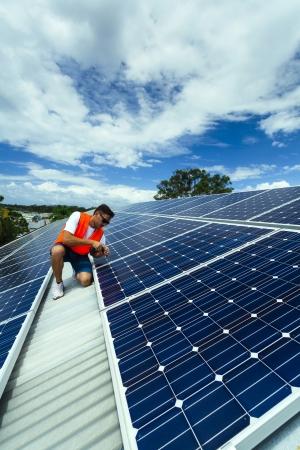 PLACAS SOLARES: Joven técnico instalación de paneles solares en el techo de la fábrica