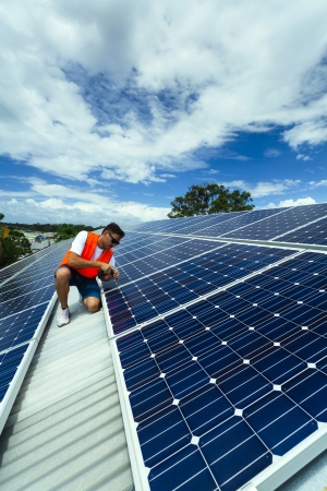 carbon neutral: Young technician installing solar panels on factory roof