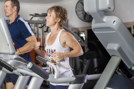 Mature couple running on tradmill at fitness centre photo