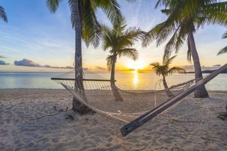 Tropisch paradijs strand bij zonsondergang met hangmat