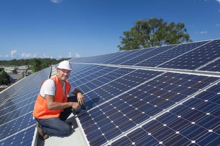 energia solar: Joven t?cnico instalaci?n de paneles solares en el techo de la f?brica