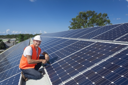 photovoltaic: Young technician installing solar panels on factory roof