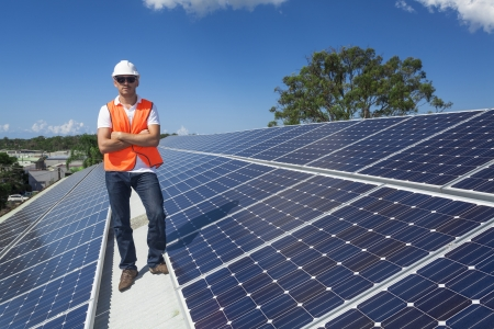 Young technician standing with solar panels on factory roof photo