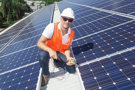 Young technician installing solar panels on factory roof photo