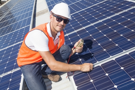 solar array: Young technician installing solar panels on factory roof