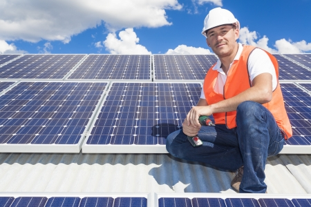 electric grid: Young technician installing solar panels on factory roof