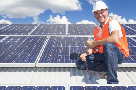energy work: Solar panel technician on roof