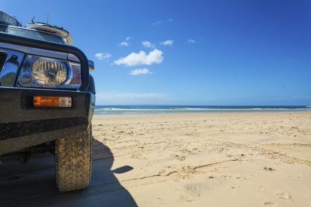 Off road vehicle with surfboard on roof parked on tropical beach photo