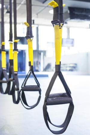 Suspention training straps in fitness studio Stock Photo