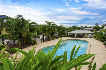 inground: Tropical swimming pool in gated community Stock Photo