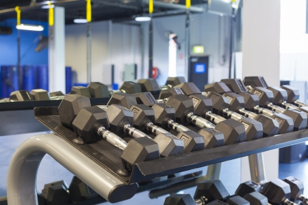 Kurzhanteln am Regal im Fitness-Studio