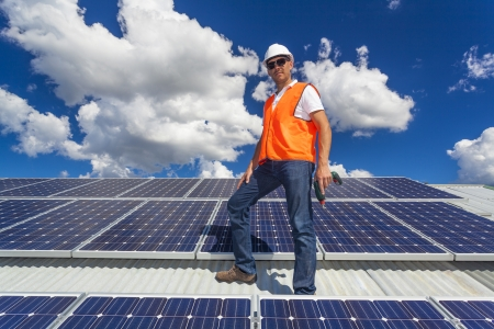 solar array: Young technician checking solar panels on factory roof