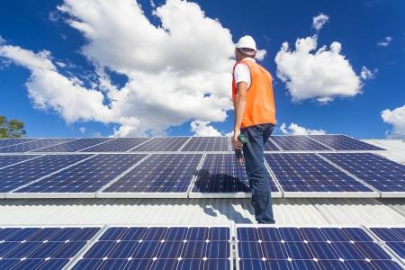 PLACAS SOLARES: Técnico joven que controla los paneles solares en el techo de la fábrica Foto de archivo