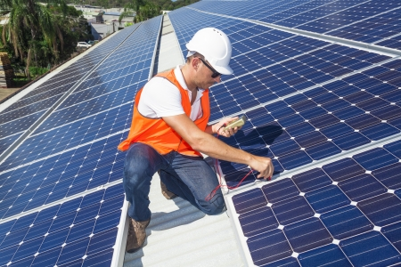 Young technician checking solar panels on factory roof photo