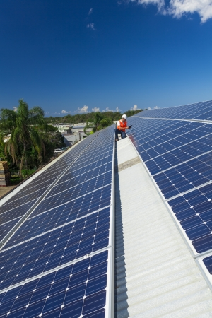 Young technician checking solar panels on factory roof Stock Photo - 21361837