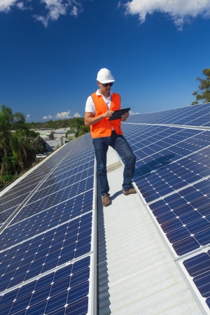 carbon neutral: Young technician checking solar panels on factory roof