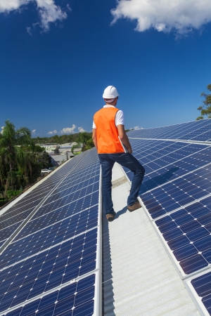 Young technician checking solar panels on factory roof Stock Photo - 21361830