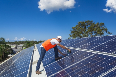 젊은 기술자가 공장 지붕에 태양 전지 패널을 설치 스톡 콘텐츠
