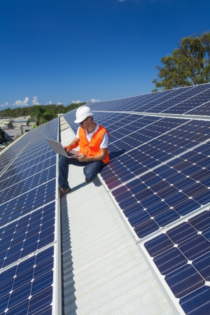 Young technician checking solar panels on factory roof Stock Photo - 21361834