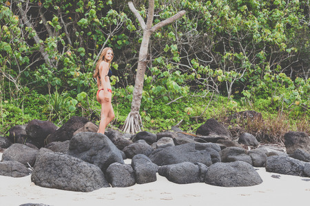 Bikini girl on tropical beach alone photo