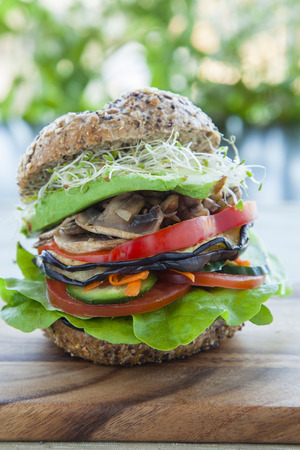 wholemeal: Vegan burger with alfalfa, avocado, mushrooms, capsicum, eggplant, tomatoes and lettuce. Stock Photo