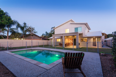 home exterior: Modern home at dusk with swimming pool Stock Photo