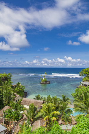 fale: Tropical Samoan resort with clear blue waters, white sand and coconut palms Stock Photo