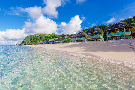 fale: Samoan Beach fales overlooking white sandy beach and blue waters